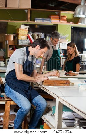 Mid adult man using holing machine while colleagues standing in background at factory