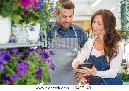 Male and female florists using digital tablet in flower shop