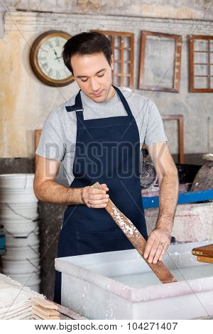 Male worker stirring pulp and water with wood in paper factory