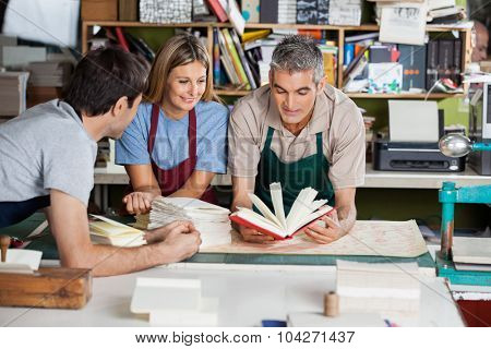 Male and female workers analyzing notebook together in factory