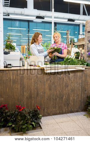 Florists making bouquet at counter in flower shop