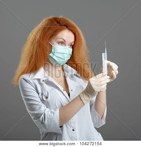 Healthcare And Medical Concept - Female Doctor Or Nurse In Medical Mask Holding Syringe With Injecti