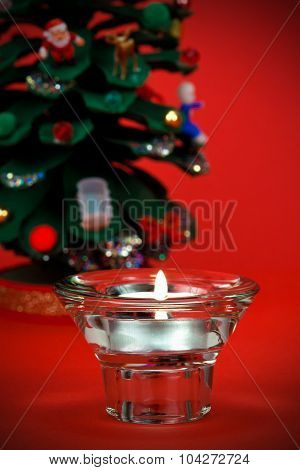 Beautiful votive candle with Christmas detail in the background