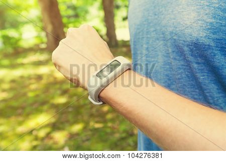 Male Runner Jogging Outside Looking At His Wearable Fitness Tracker