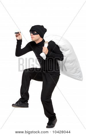 Full Length Portait Of A Robber With A Bag And Flashlight In Hands