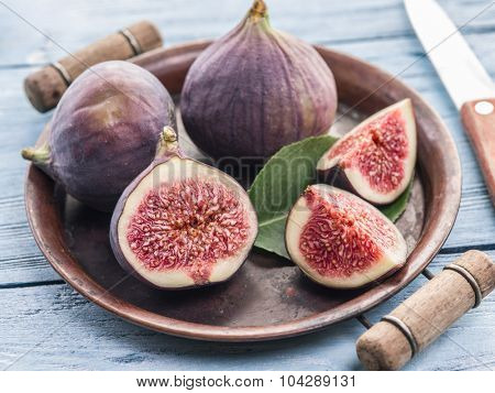 Ripe fig fruits on in the old tray on the wooden table.