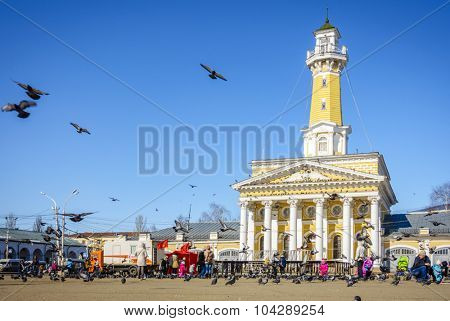 Kostroma, Russia - March 26, 2015: Pigeons flying over 18th century central square named after Ivan Susanin - a Russian national hero