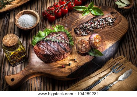 Beef steaks with spices on a wooden tray. Barbecue food.