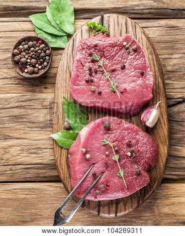 Raw beef steaks with spices on a wooden board.