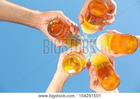 Bottles of beer in people's hands on blue sky background