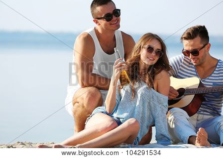 Young people with guitar singing songs on the riverside