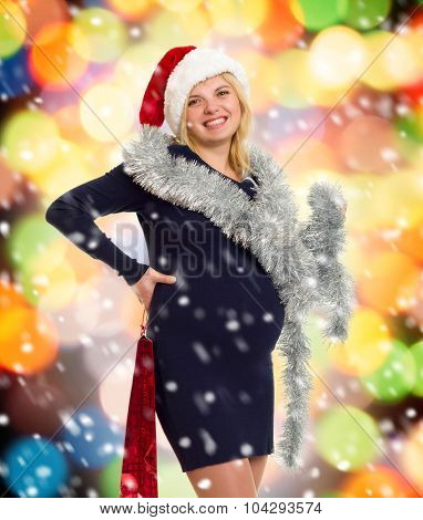 christmas holiday pregnant woman in santa hat on colorful background with shopping bag and snow