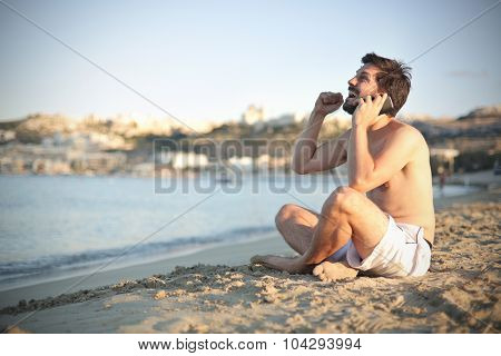 Happy man doing a phone call at the beach