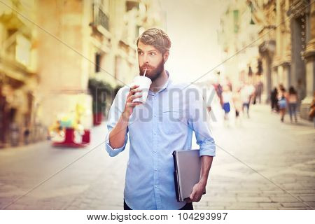 Handsome man drinking a milkshake in the street