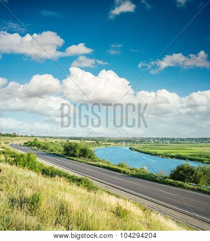 asphalt road and river in green landscape under clouds in blue sky