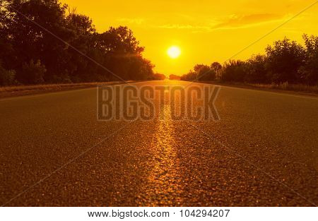 orange sunset and asphalt road. soft focus