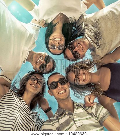 Group of friends on the beach under sunlight.