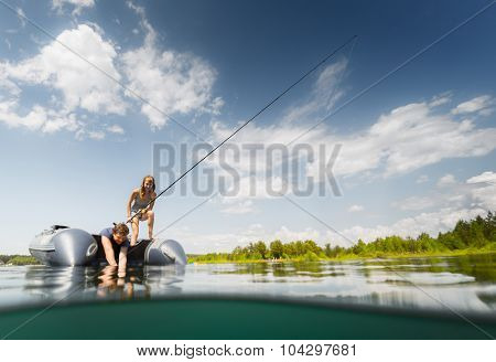 Couple fishing from the boat on the lake at sunny day. Split shot with underwater view, focus on the people