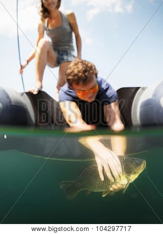 Couple fishing from the boat. Split shot with underwater view of the man holding the fish. Focus on the fish, people are blurred