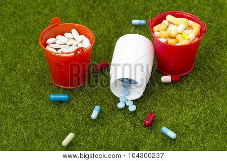 Pills,white bottle of pills and two buckets filled with colorful tablets