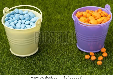 Pharmaceutical concept. Two buckets filled with orange and blue pills