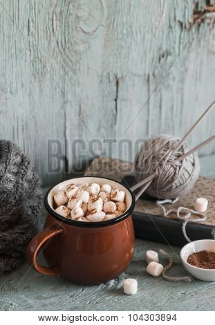 Hot Chocolate With Marshmallows In A Ceramic Cup, Old Book, Yarn And Needles On A Light Wooden Surfa