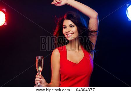 people, holidays, party, night lifestyle and leisure concept - beautiful sexy woman in red dress with champagne glass dancing at nightclub