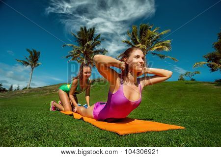 Slim fitness young woman Athlete girl training her muscular back outside. Concept training workout crossfit gymnastics cross fit.