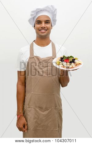 Male chef with cheese plate with grapes, nuts and strawberry