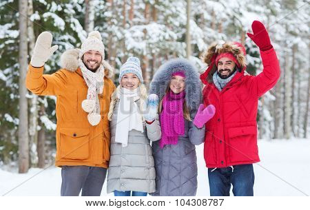 love, relationship, season, friendship and people concept - group of smiling men and women waving hands in winter forest
