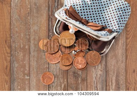 finance, cash, money saving and investment concept - close up of euro coins and wallet on wooden table