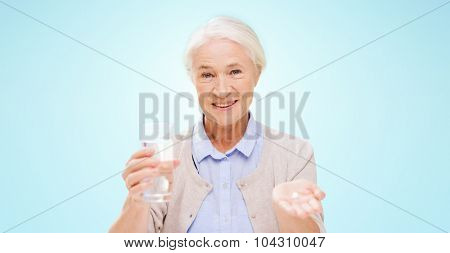 age, medicine, health care and people concept - happy senior woman with pills and glass of water over blue background