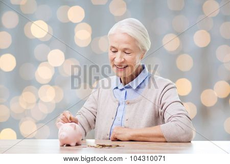 savings, money, annuity insurance, retirement and people concept - smiling senior woman putting coins into piggy bank over holidays lights background