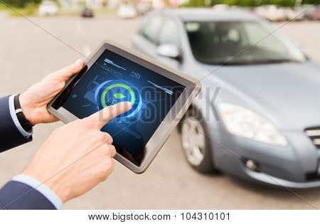 transport, business trip, technology and people concept - close up of male hands setting eco driving mode on tablet pc computer and car outdoors