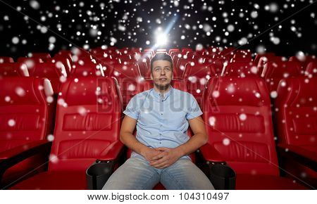 cinema, entertainment and people concept - happy young man watching movie alone in empty theater auditorium over snowflakes