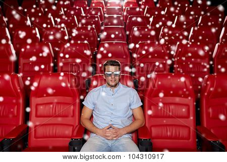 cinema, technology, entertainment and people concept - happy young man with 3d glasses watching movie alone in empty theater auditorium over snowflakes