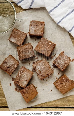 chocolate brownie diced baking paper on wooden table with a towel