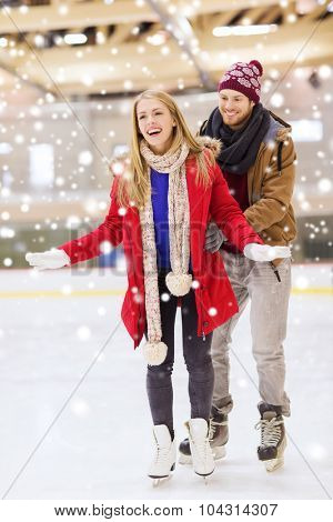people, friendship, sport and leisure concept - happy couple on skating rink