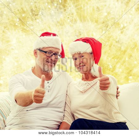 family, holidays, christmas, age and people concept - happy senior couple in santa helper hats sitting on sofa over yellow lights background and showing thumbs up gesture