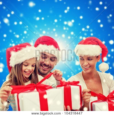 family, christmas, generation, holidays and people concept - happy family in santa helper hats with gift boxes over blue snowy background
