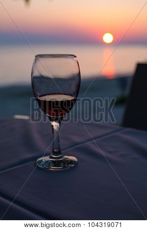 glass with red wine and Sunset on beach  at the background. summertime vacation concept