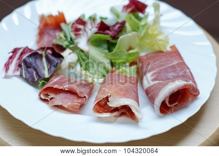 Horizontal closeup of slices of rolled cured pork ham jamon with lettuce