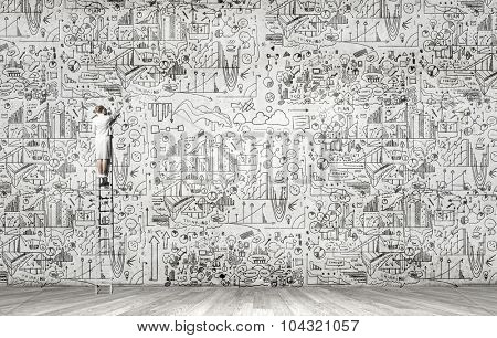 Rear view of woman standing on ladder and drawing science sketch on wall