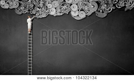 Rear view of businesswoman standing on top of ladder and reaching gears mechanism