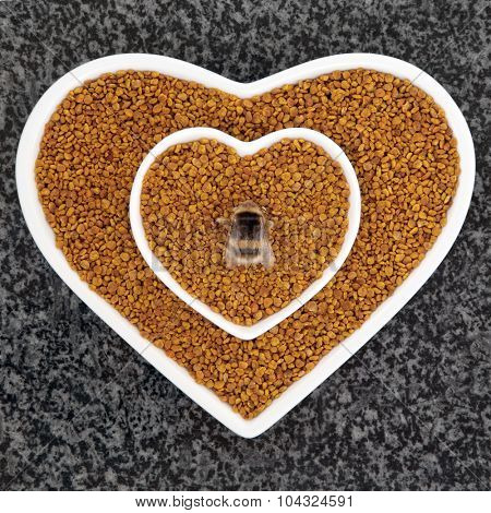 Bee pollen health food in heart shaped dishes with bumblebee over marble background.