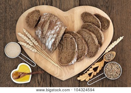 Healthy rye bread on a heart shaped board with wheat sheaths, yeast, oil, grain in love spoon and scoop over oak background.