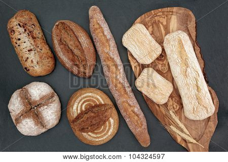 Homemade bread selection on olive wood board on slate background.