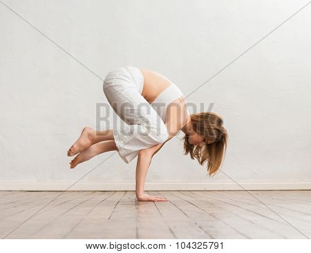 Young and sporty girl training in gym. Yoga exercise.