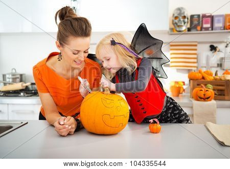 Mother With Daughter Creating Jack-o-lantern On Halloween