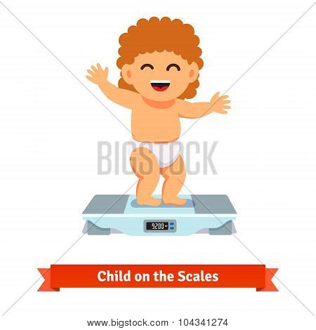Happy baby toddler in diaper weighting on a scales
